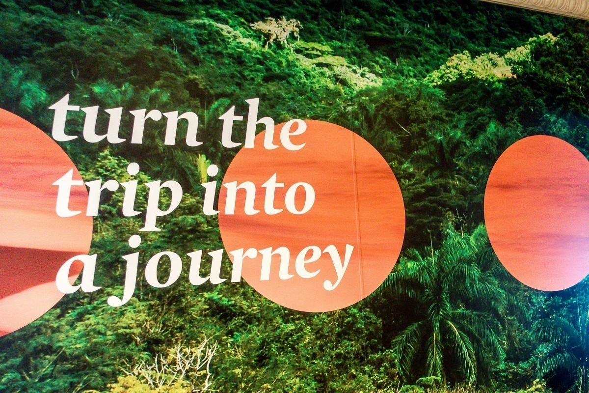 """turn the trip into a journey"" -- a poster reminder on Fathom cruise line's Adonia cruise ship"