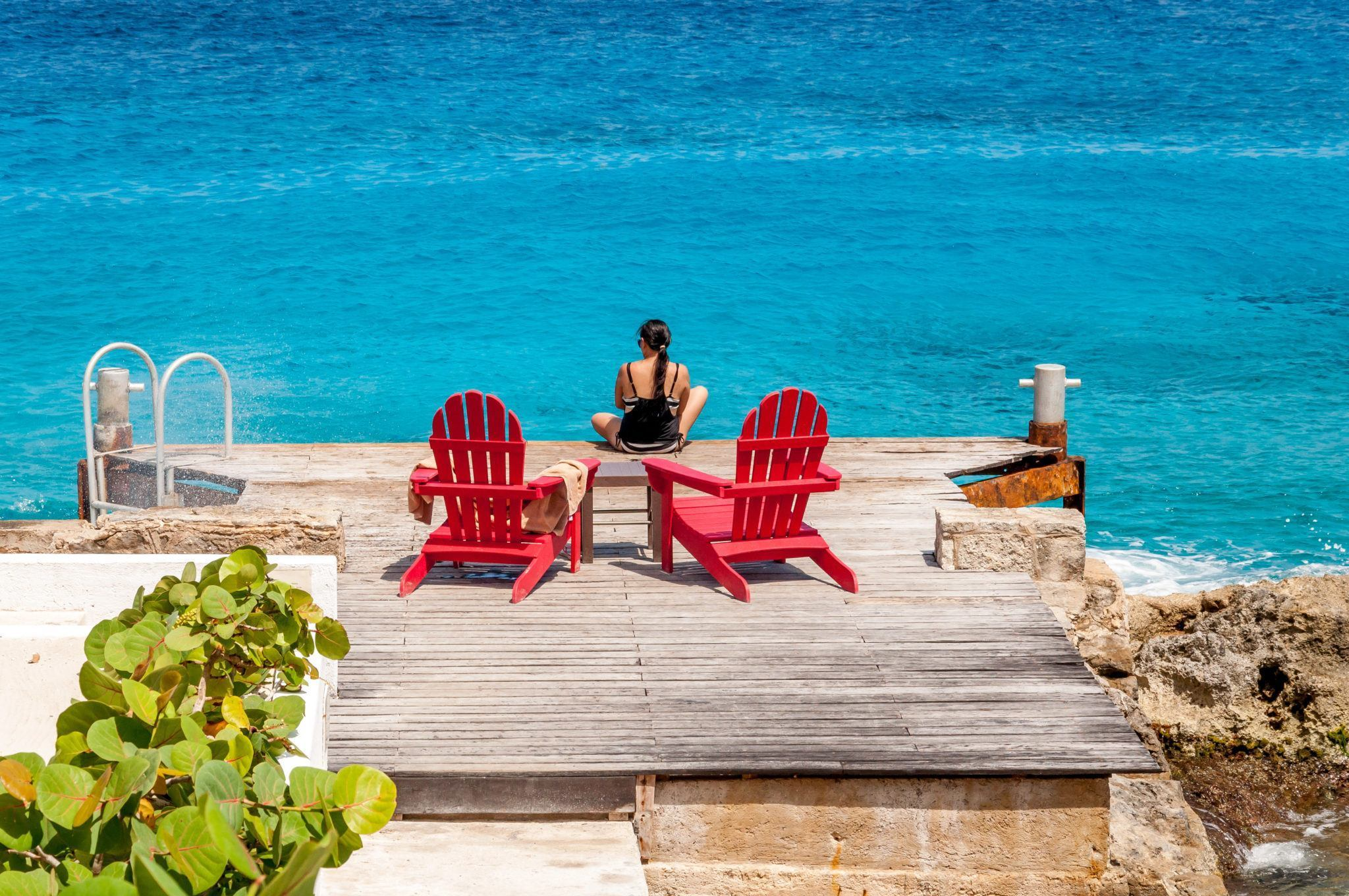 Woman sitting on a small dock with red beach chairs