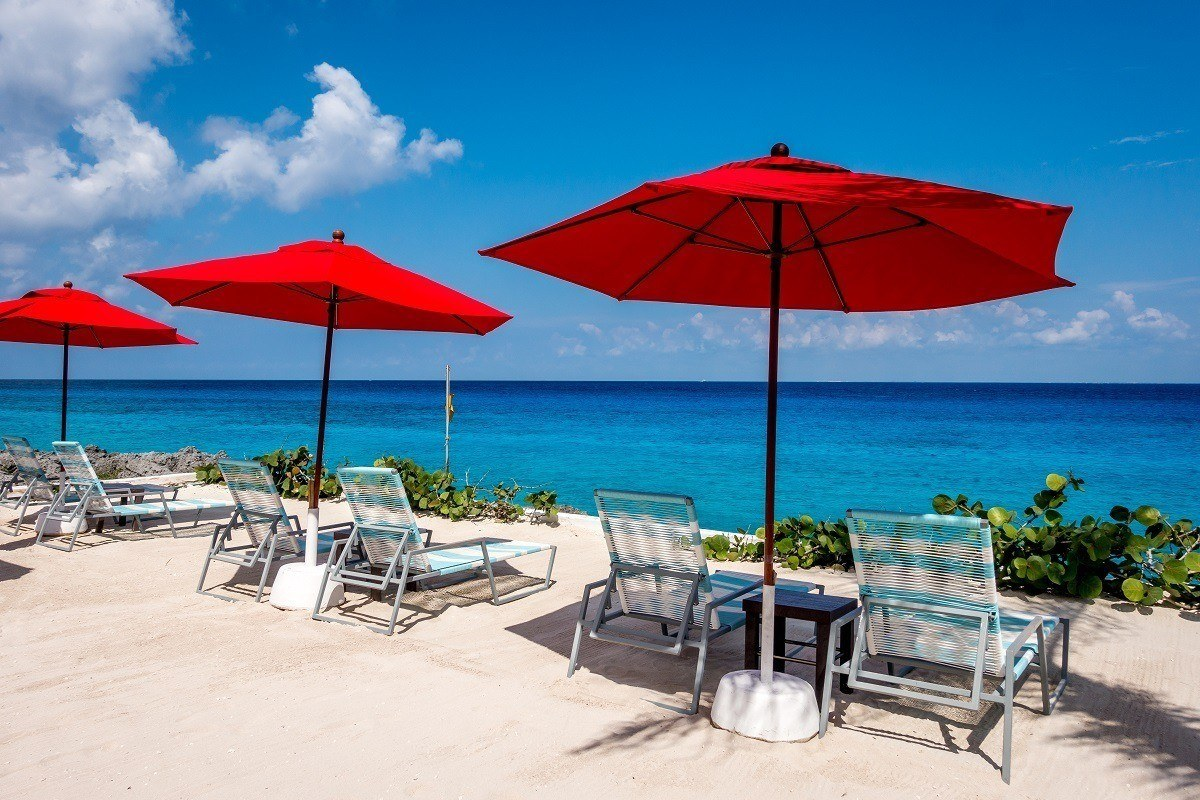Red umbrellas and lounge chairs on a beachfront terrace