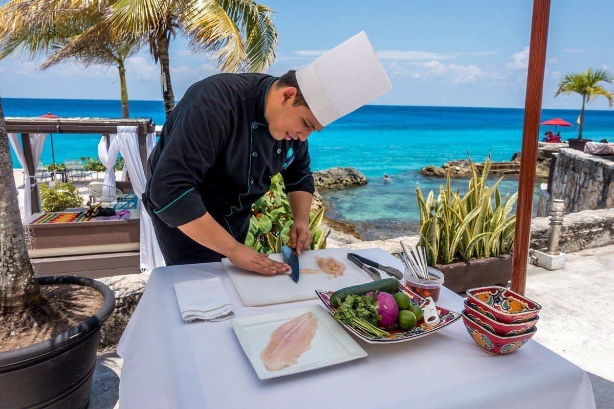 Chef cutting fish for ceviche by the ocean