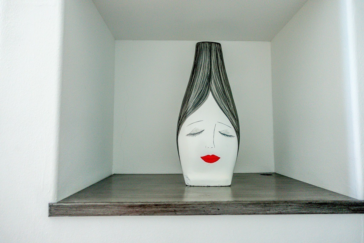 Vase painted with a womans face in the hotel room