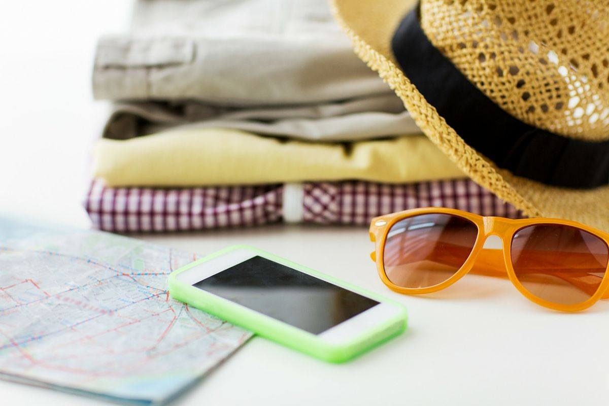 Phone, map, sunglasses, and clothes ready for a trip