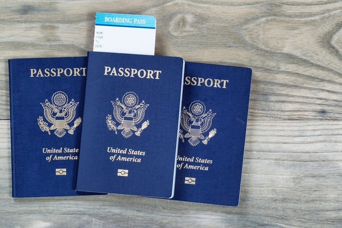 Three passports with a boarding pass for an international trip