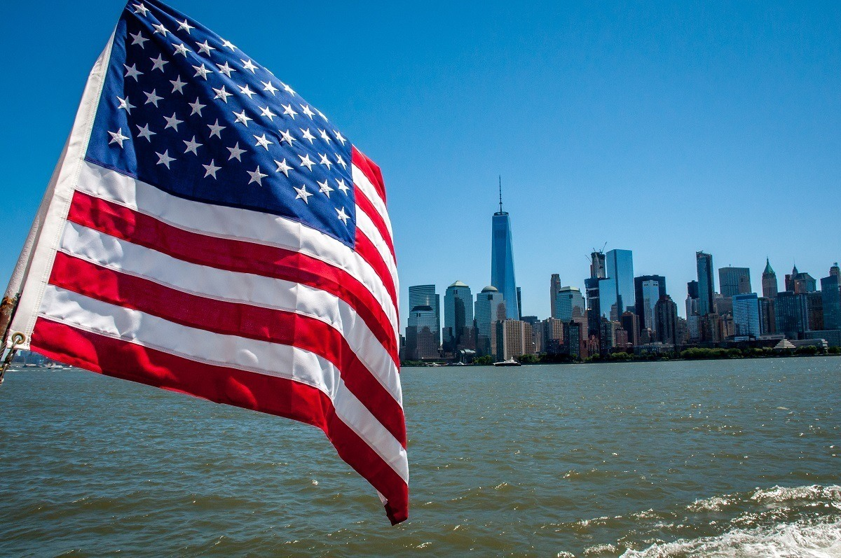An American flag flying with the New York skyline in the background.