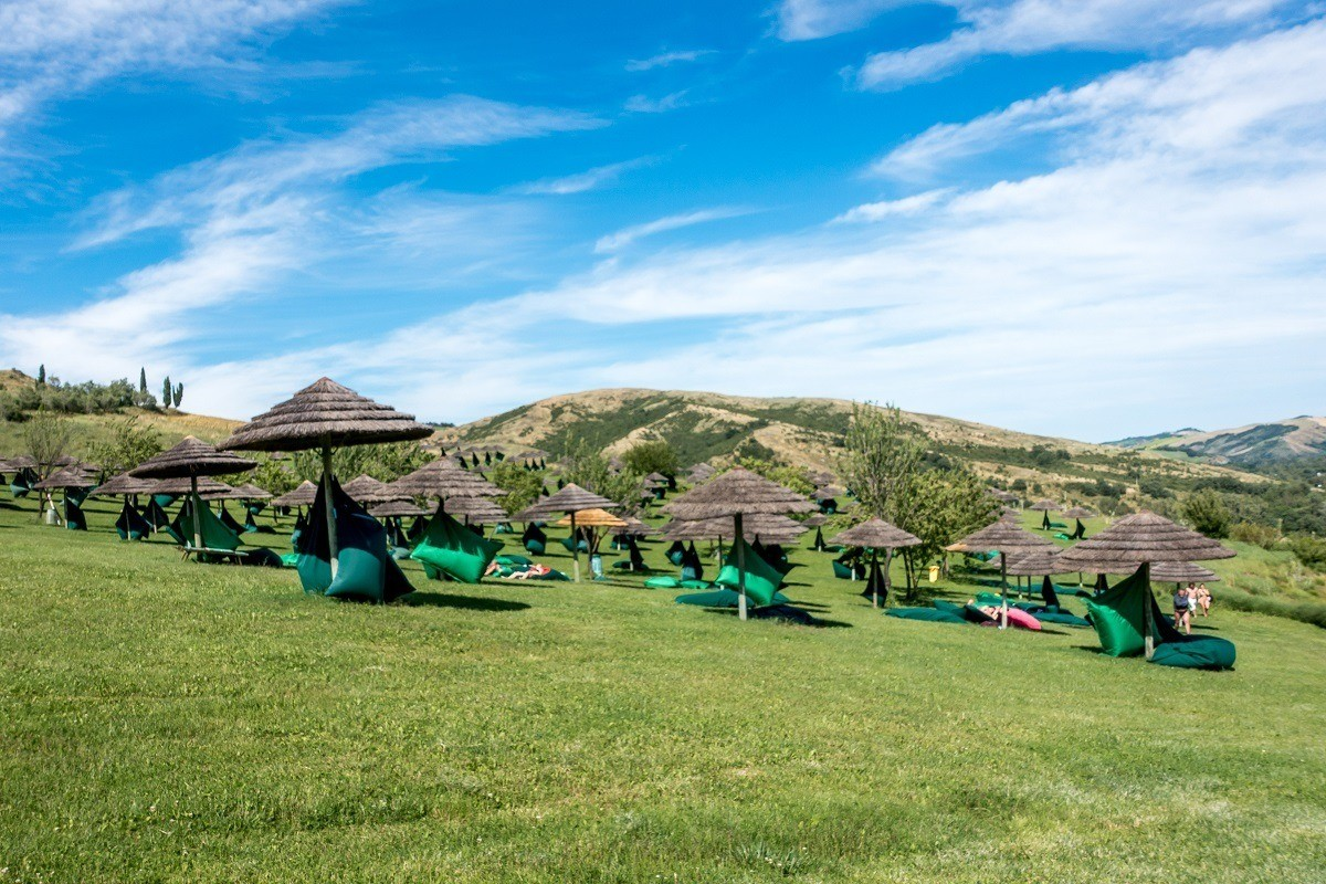 Bean bag chairs and umbrellas for relaxing on a hillside