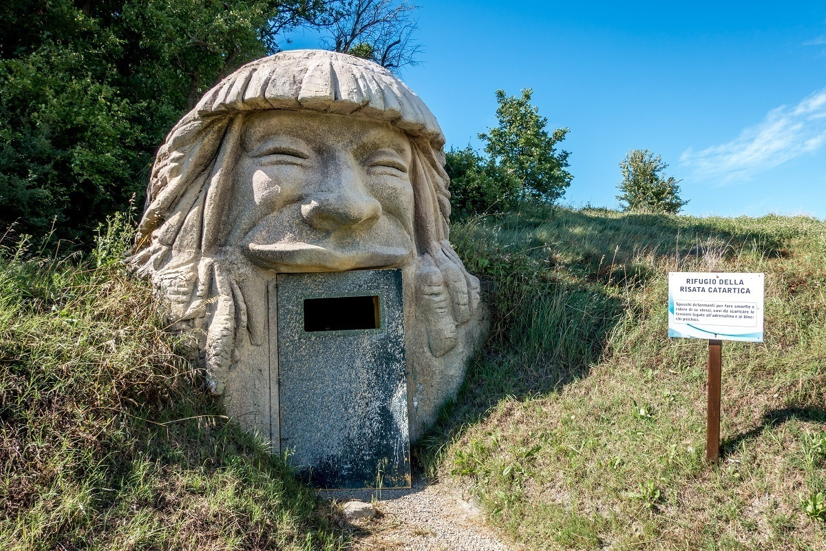 Building shaped like the head of a laughing man with a door as the mouth