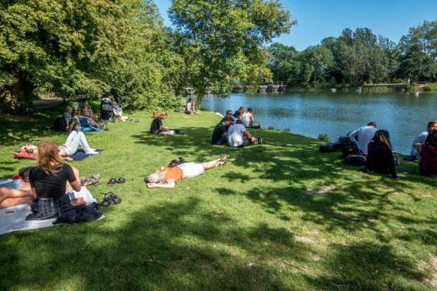 People relax by the lake in Copenhagen's Christiania commune