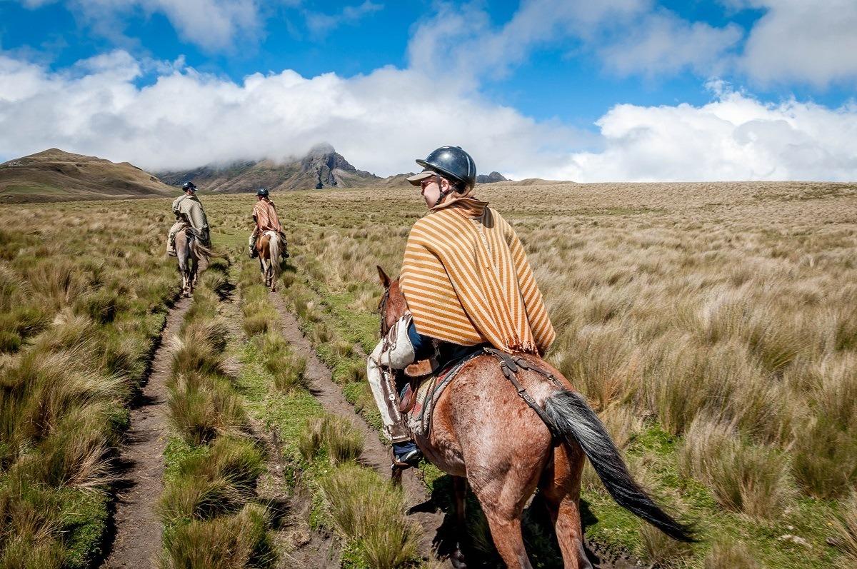 Three people riding horses through the Avenue of the Volcanoes in Ecuador