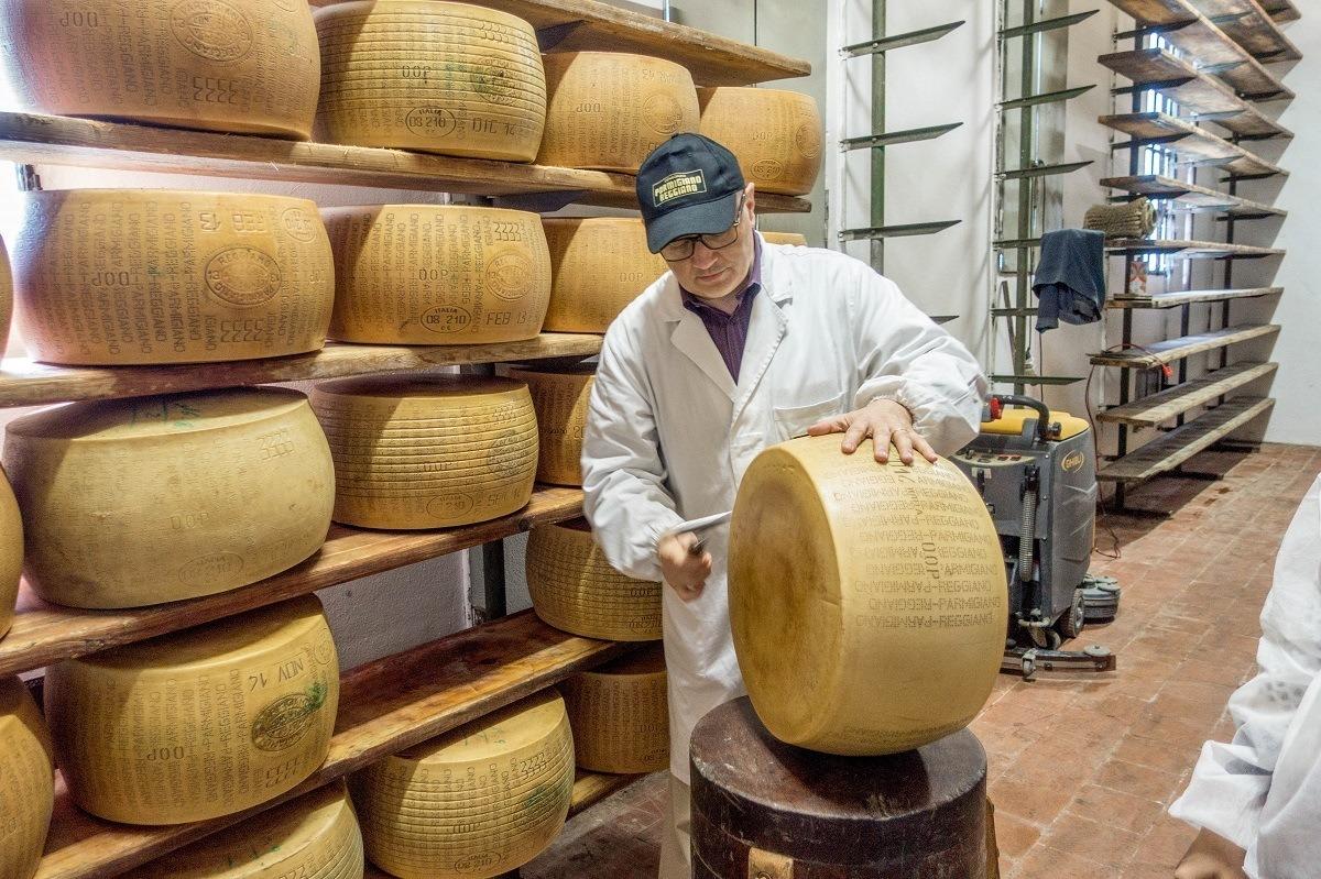 Man examining wheel of Parmigiano-Reggiano