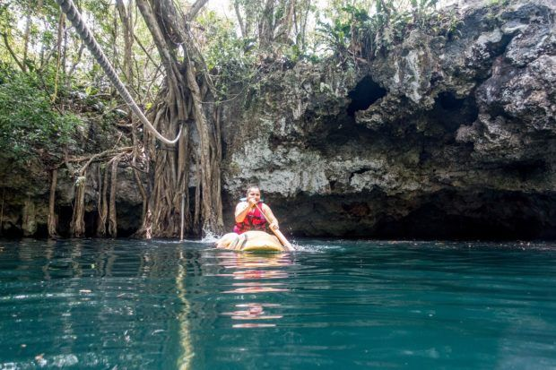 Paddling on a kayak in a open cenote on the Ruta de los Cenotes.