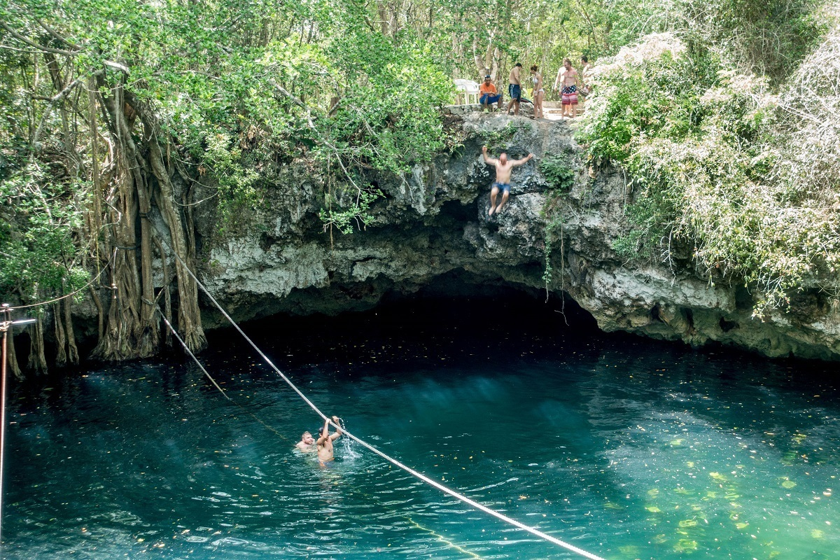 People cliff jumping at the Cenote Verde Lucero into the water below