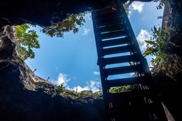 Looking up at the sky from inside a closed cenote.