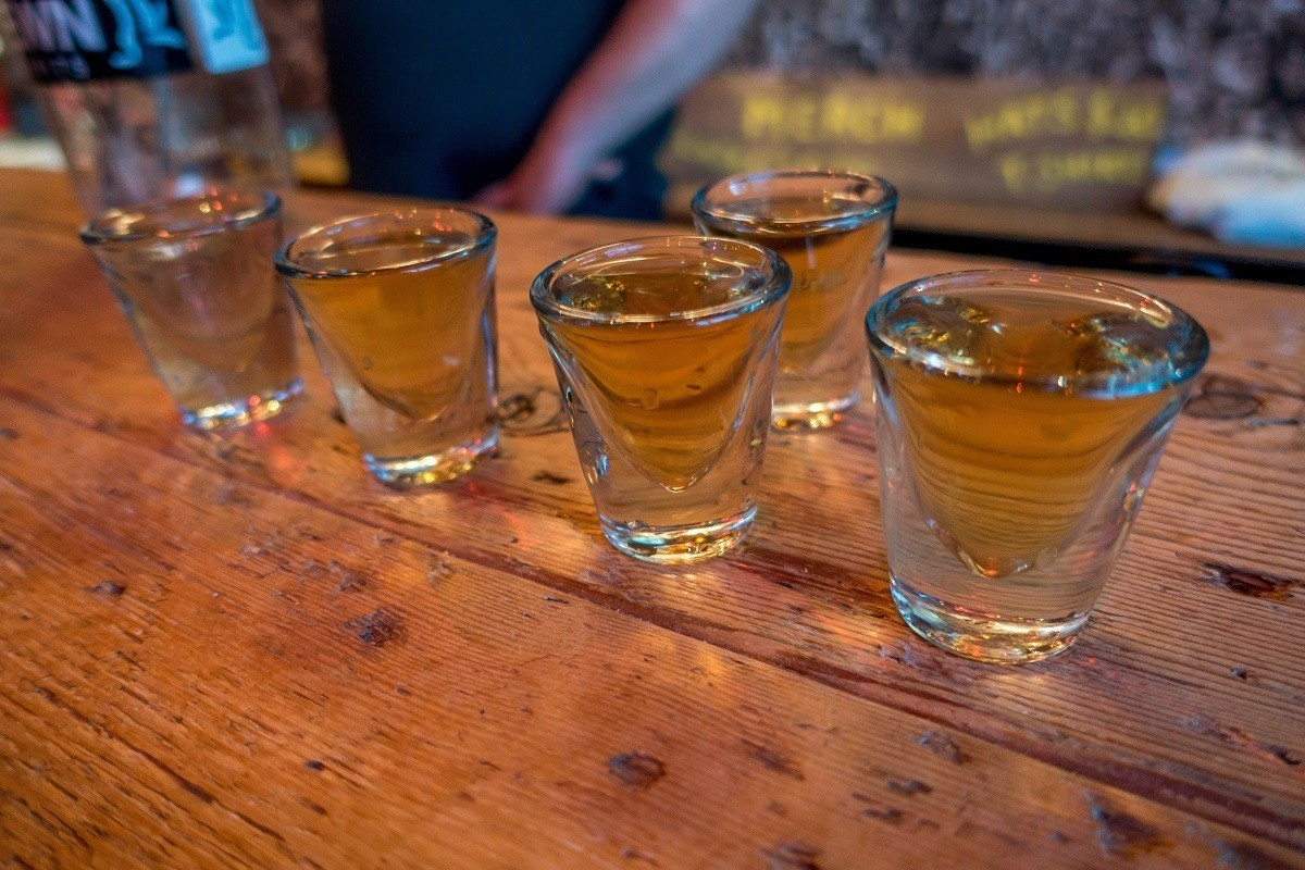 Five shot glasses full of spirits on a wooden bar