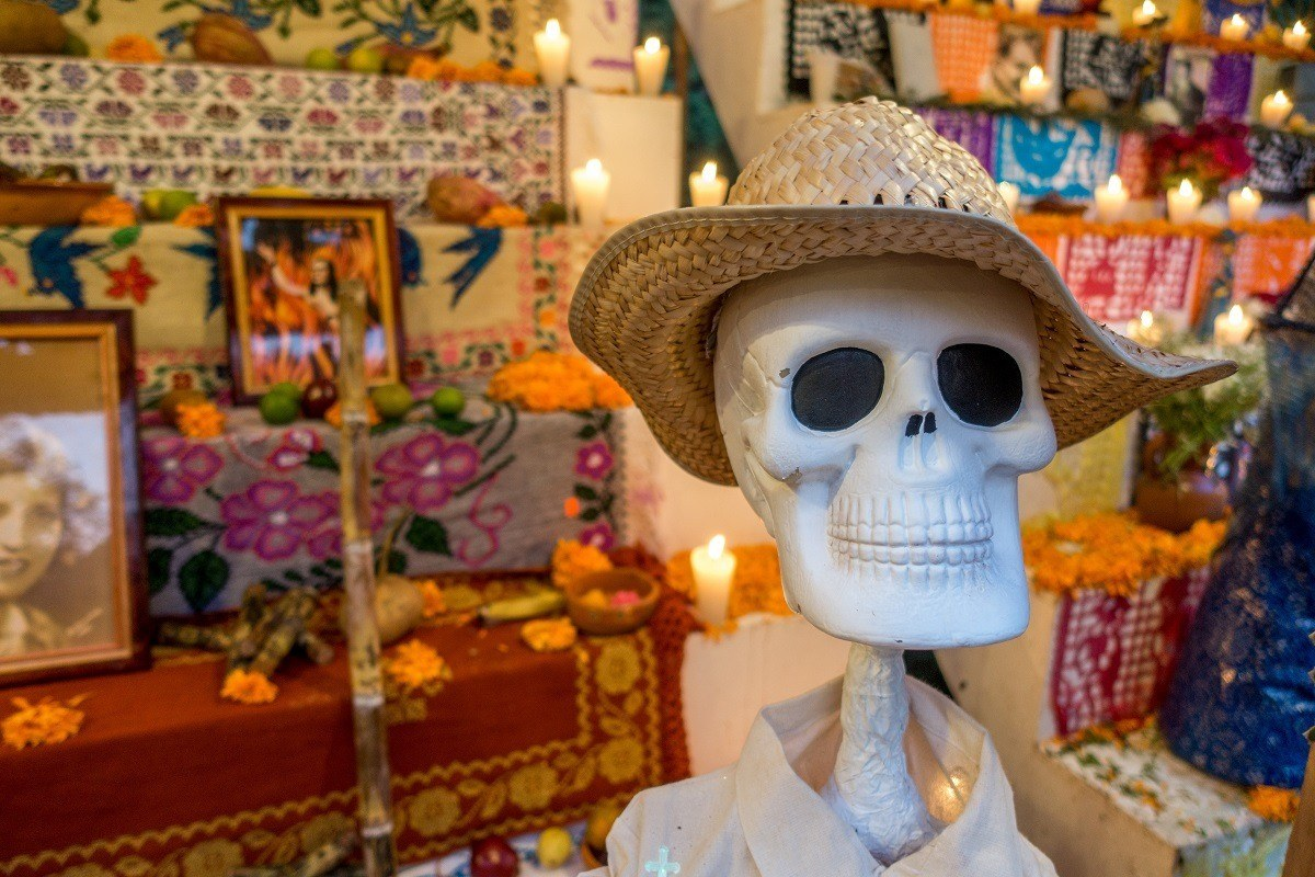 Fake skeleton in front of an altar with candles