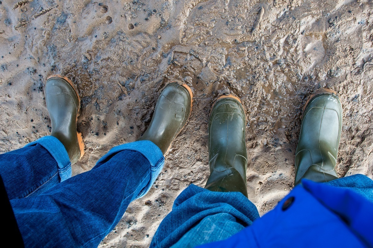 Two people in mud boots standing in the mud on the salt flats