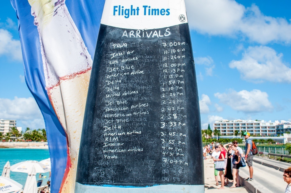 Schedule of planes landing at Maho Beach written on a surfboard