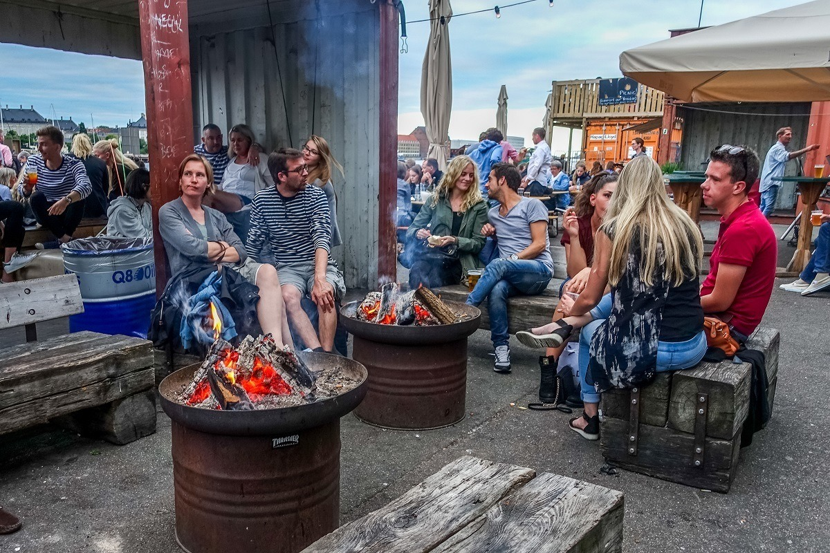People sitting by firepits at Copenhagen Street Food