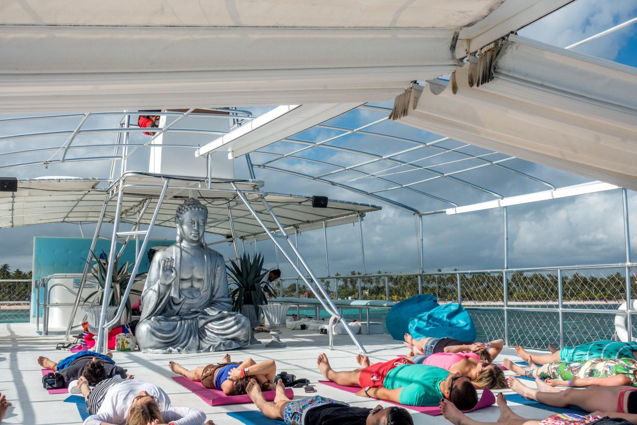 People doing yoga on a boat in front of Buddha statue