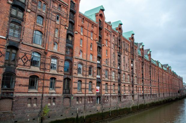 A long line of red-brick warehouses, part of the Speicherstadt district in Hamburg, Germany