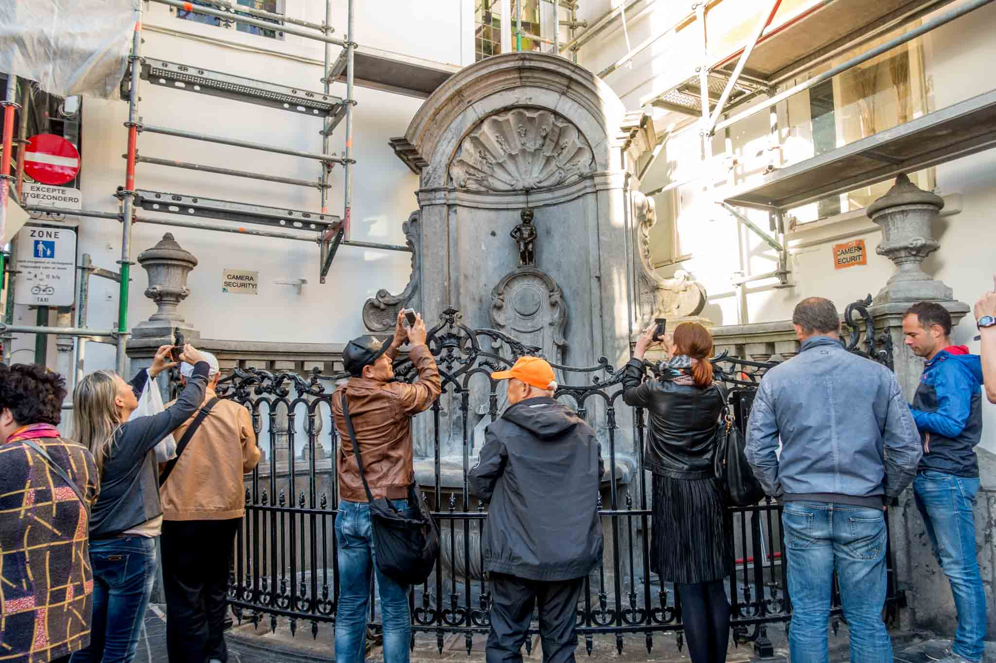 Tourists photographing Manneken Pis, statue of a little boy peeing