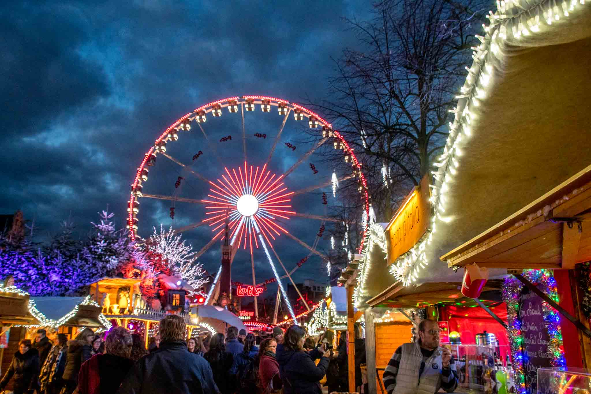 Ferris wheel, vendors, and shoppers at Brussels Christmas market