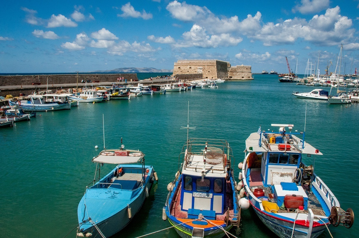 Colorful boats and stone fortress in the harbor of Heraklion