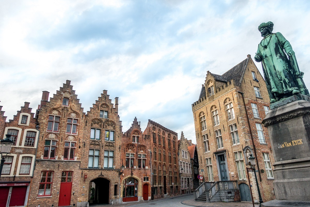 Statue of artist Jan Van Eyck and the unique architecture of Bruges