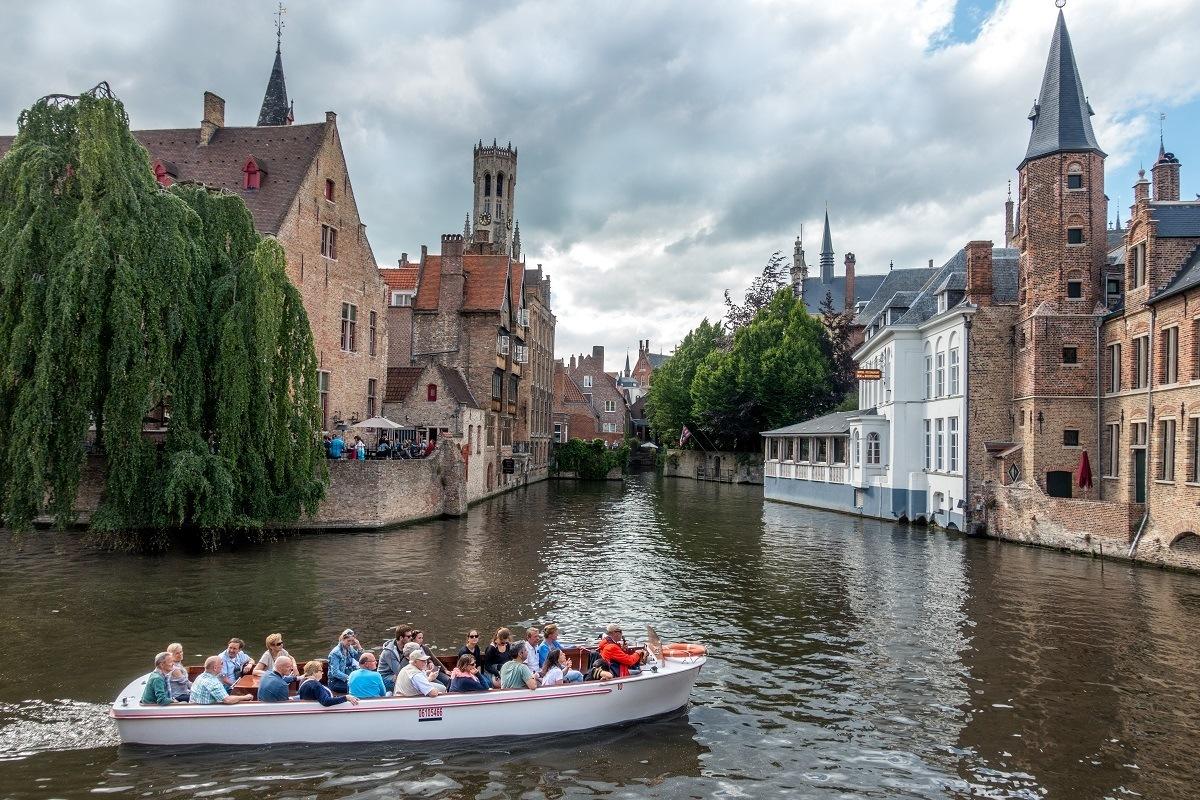 Boat cruising between two buildings in Bruges