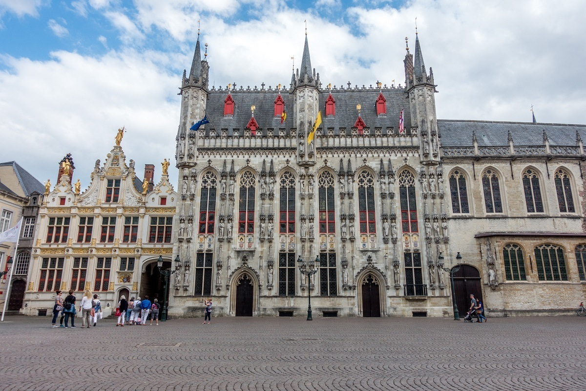Gray building with turrets and stained glass windows, the Bruges Town Hall