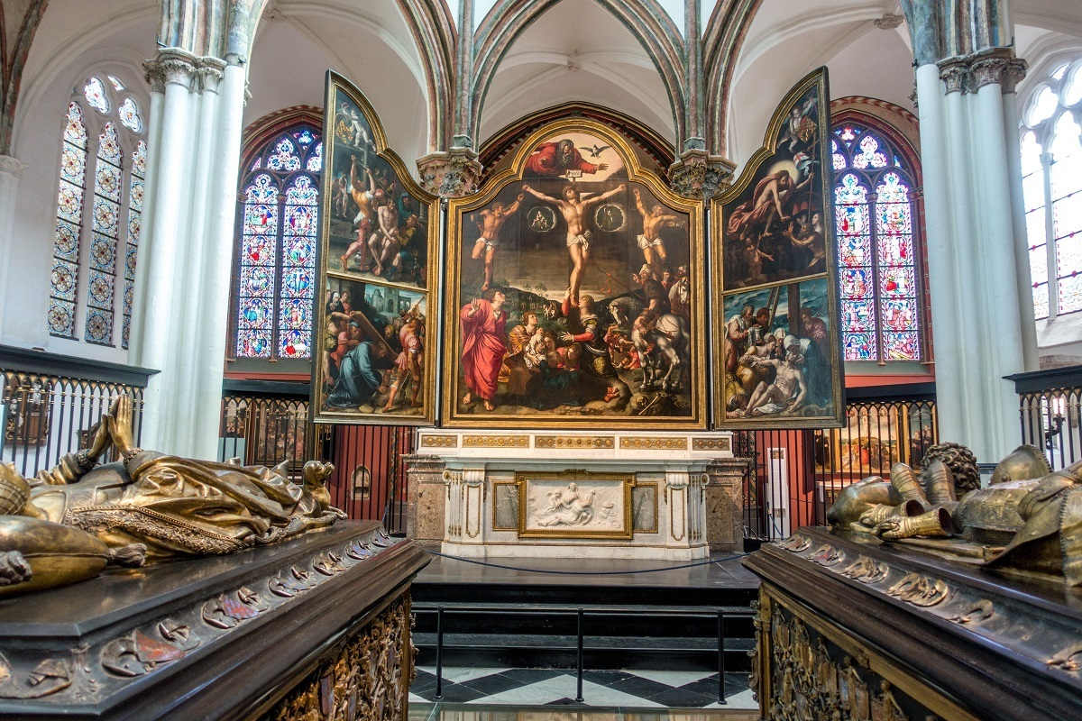 Religious painting in front of stained glass windows