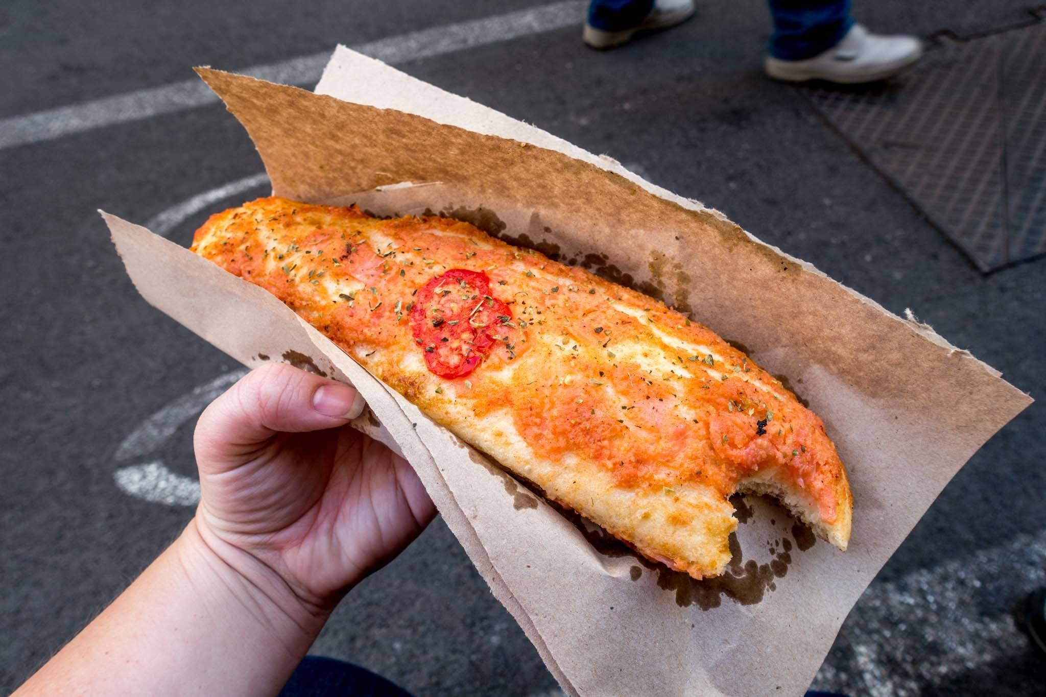 Bread covered in melted cheese and tomato sauce, a Palermo street food