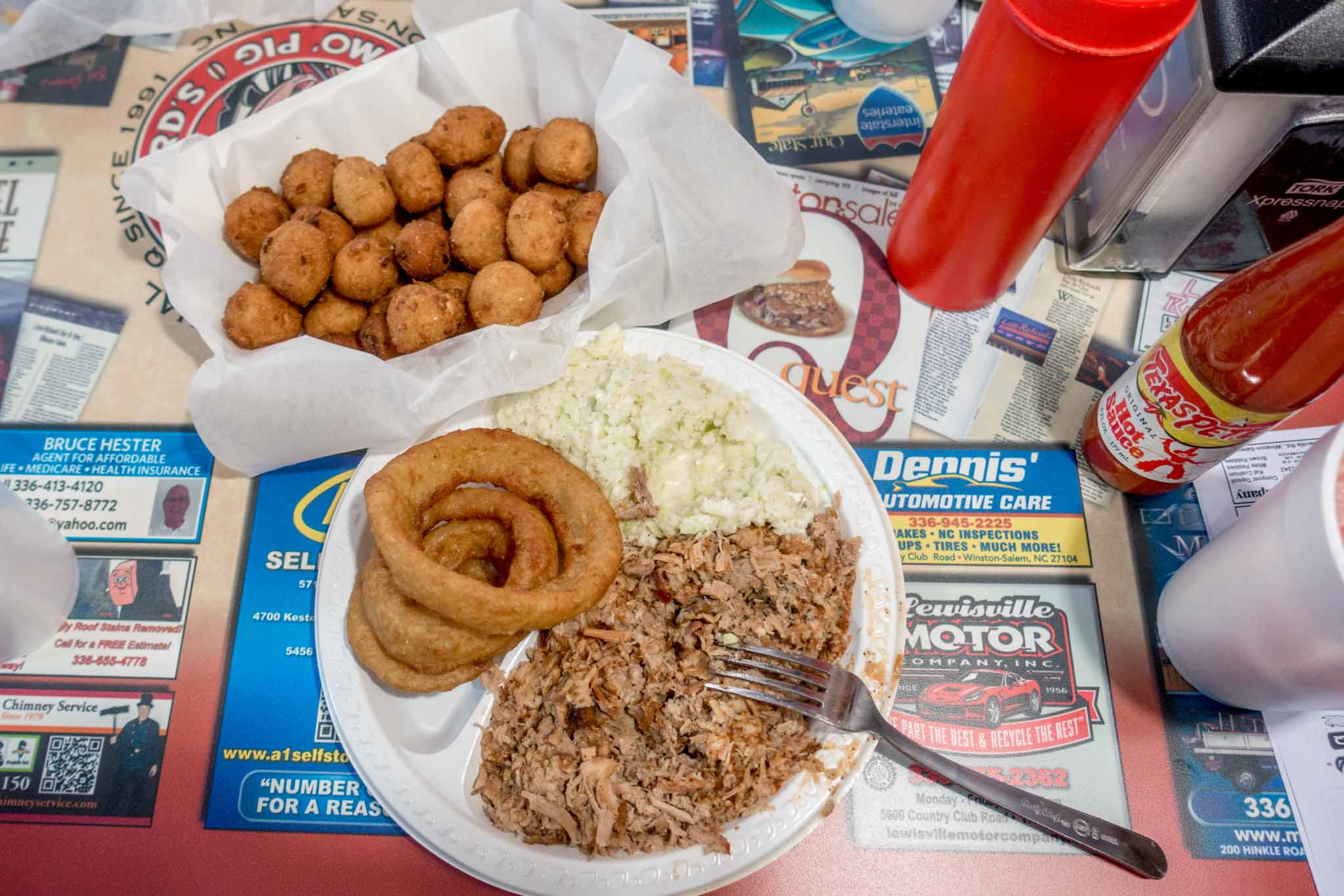 Barbecue, onion rings, and hushpuppies on plates