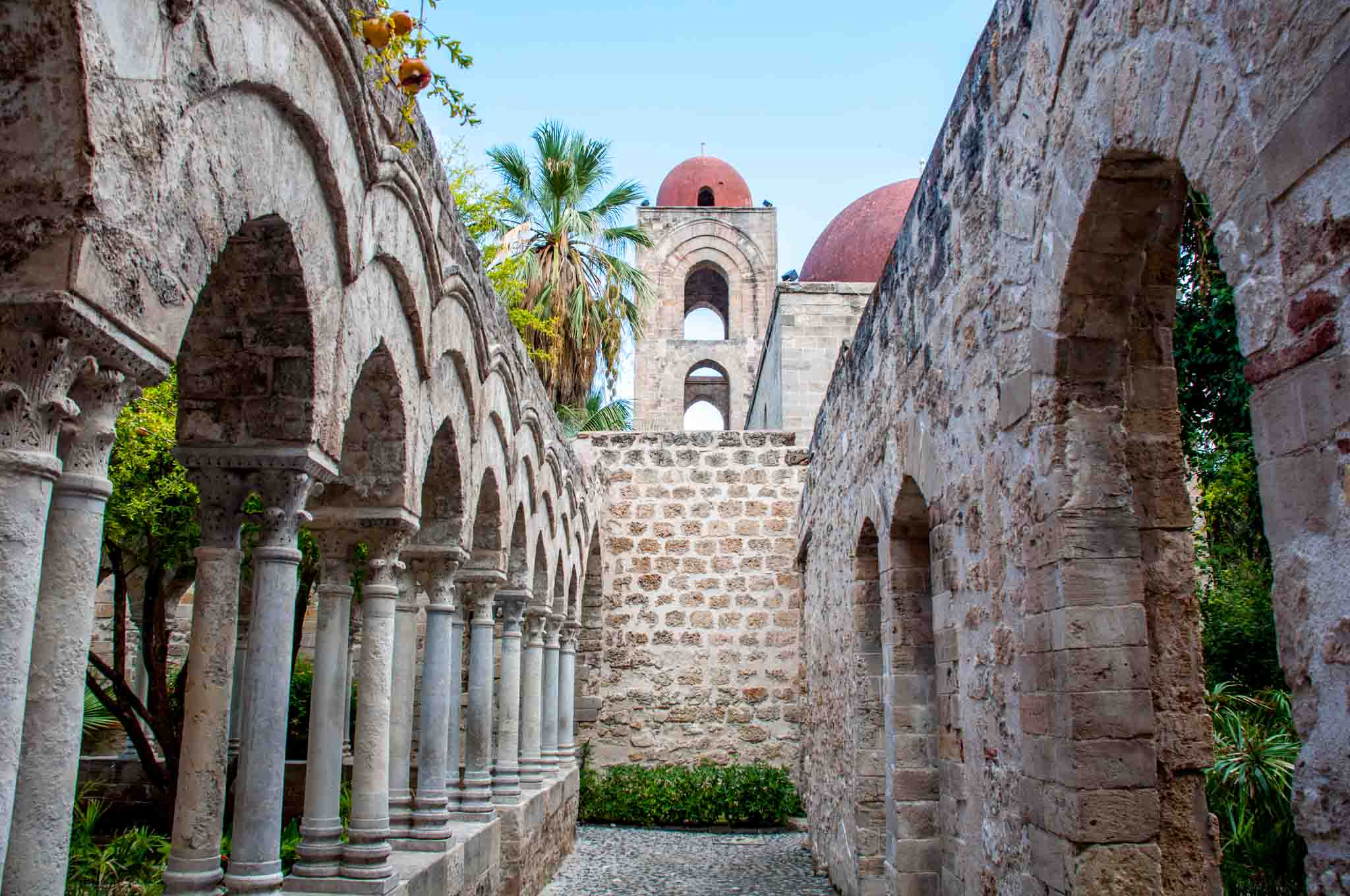 Arches in courtyard of St. John of the Hermits and tower topped with red dome