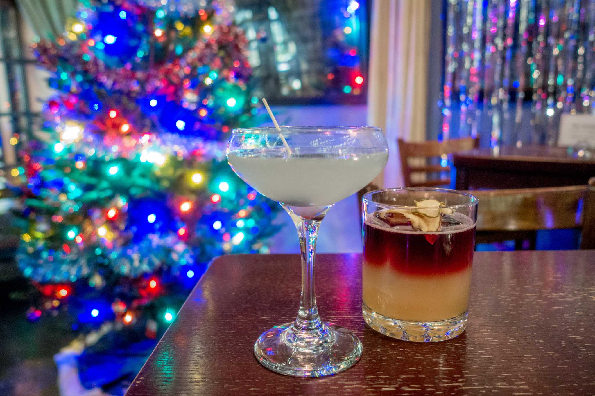 Cocktails on a table in front of a Christmas tree