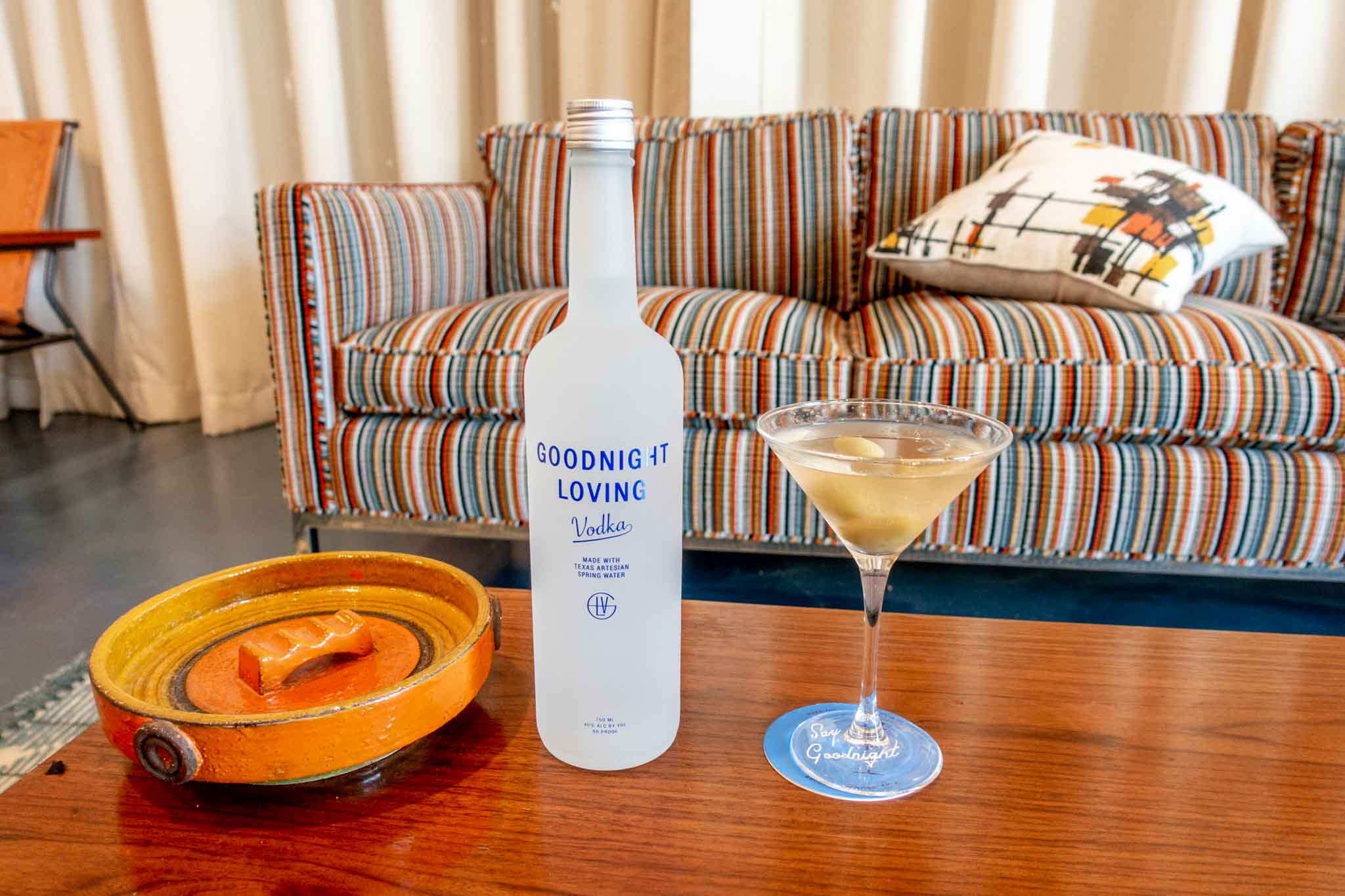 Bottle of Goodnight Loving vodka and martini in 1960s-inspired room