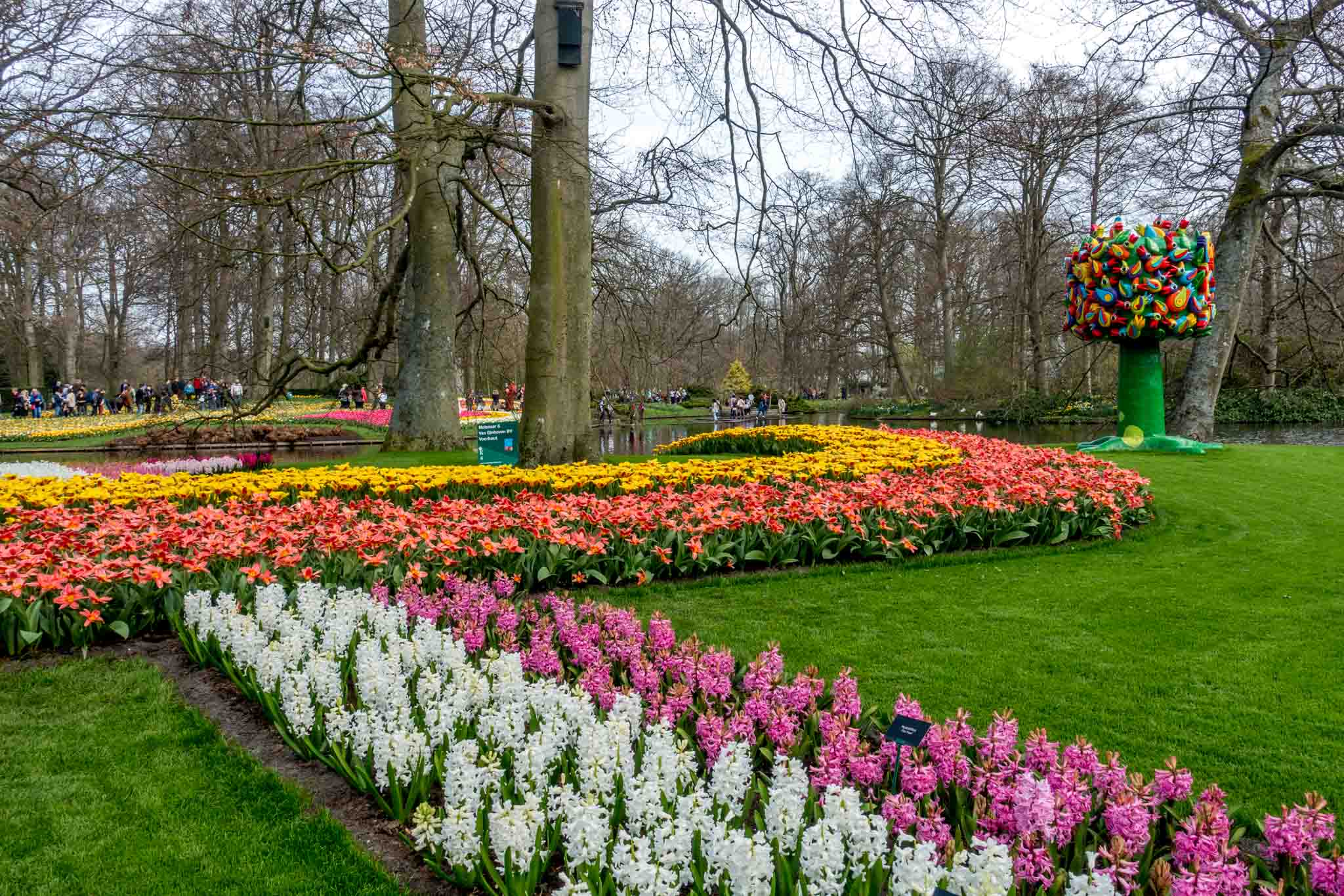 Colorful sculpture beside rows of bright flowers at Keukenhof