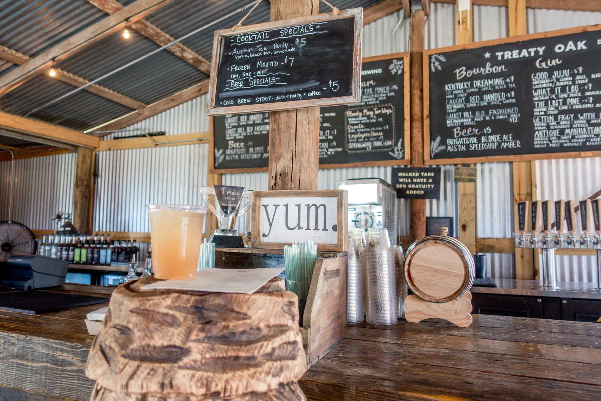 Menu, bar, and drink at Treaty Oak Distillery
