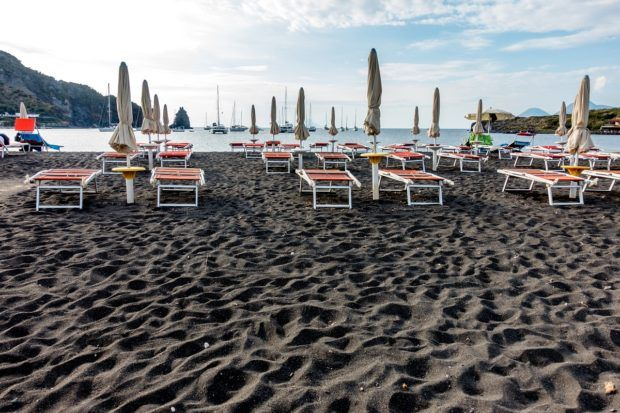 Relaxing on the black sand beach on Vulcano Sicily in Italy