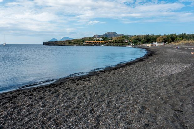 Relax at Porto di Ponente on the Spiaggia Sabbia Nera: a black sand beach Italy.