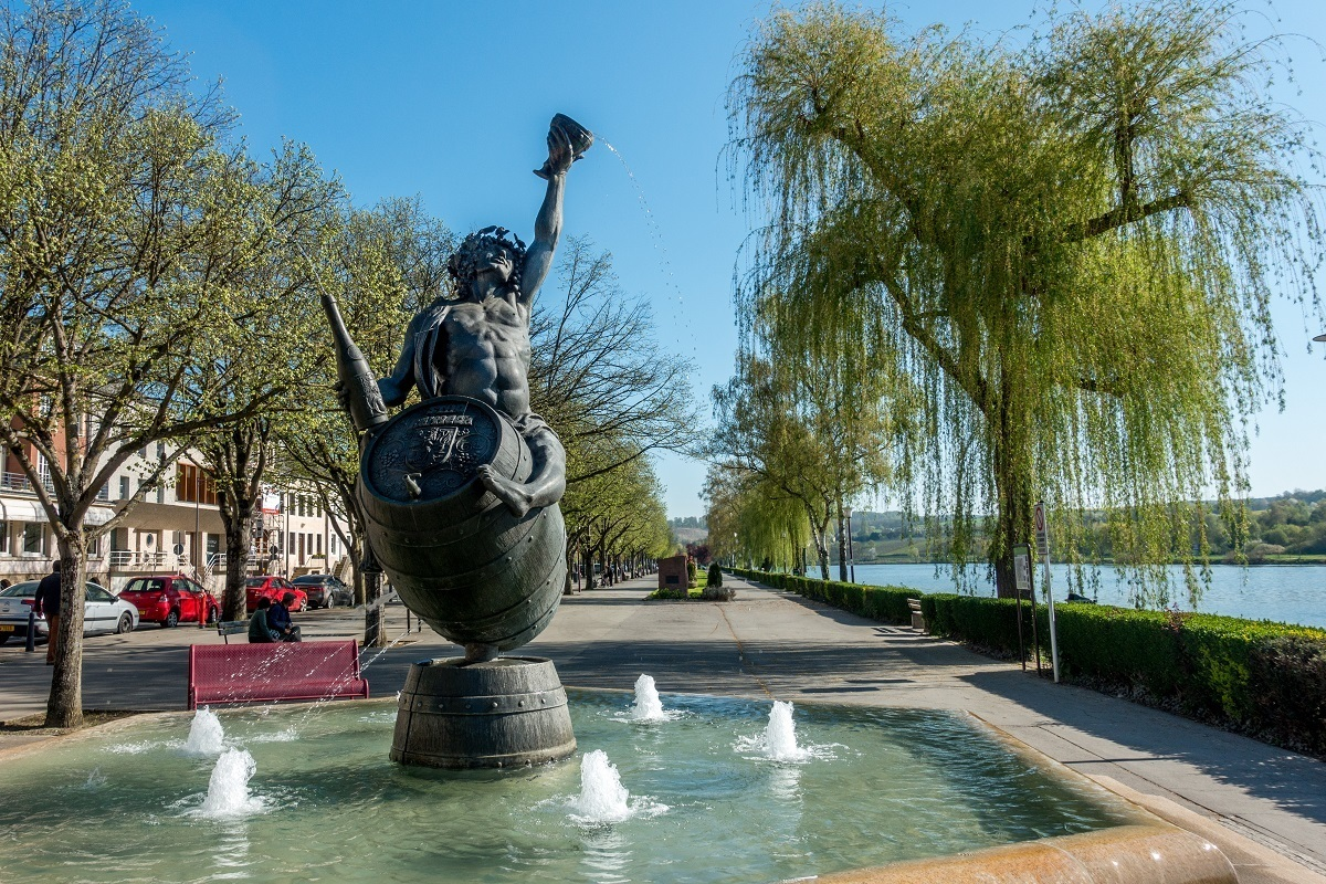 Bacchus fountain near river in Remich, Luxembourg
