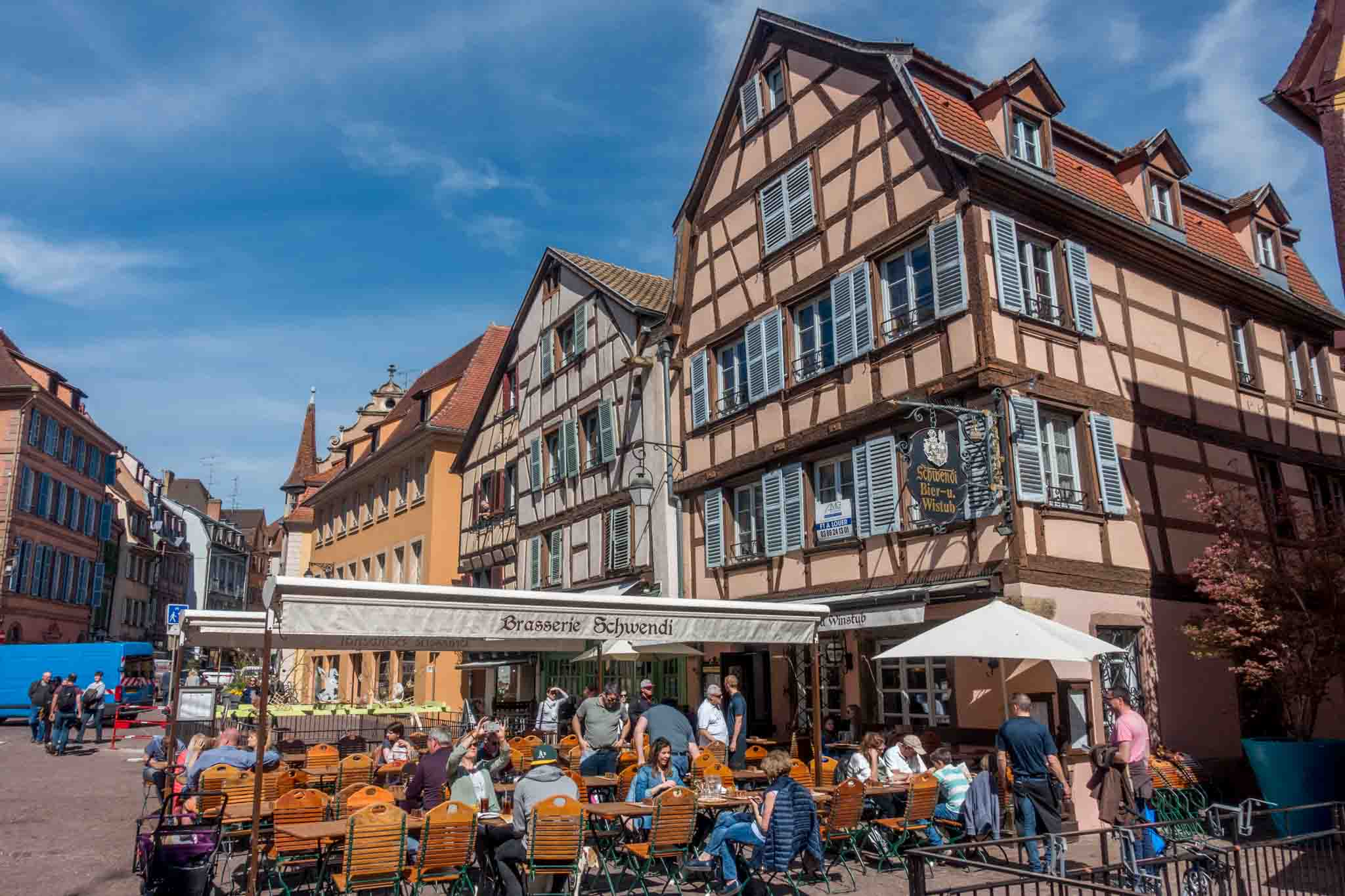 People eating at an outdoor cafe in a town square