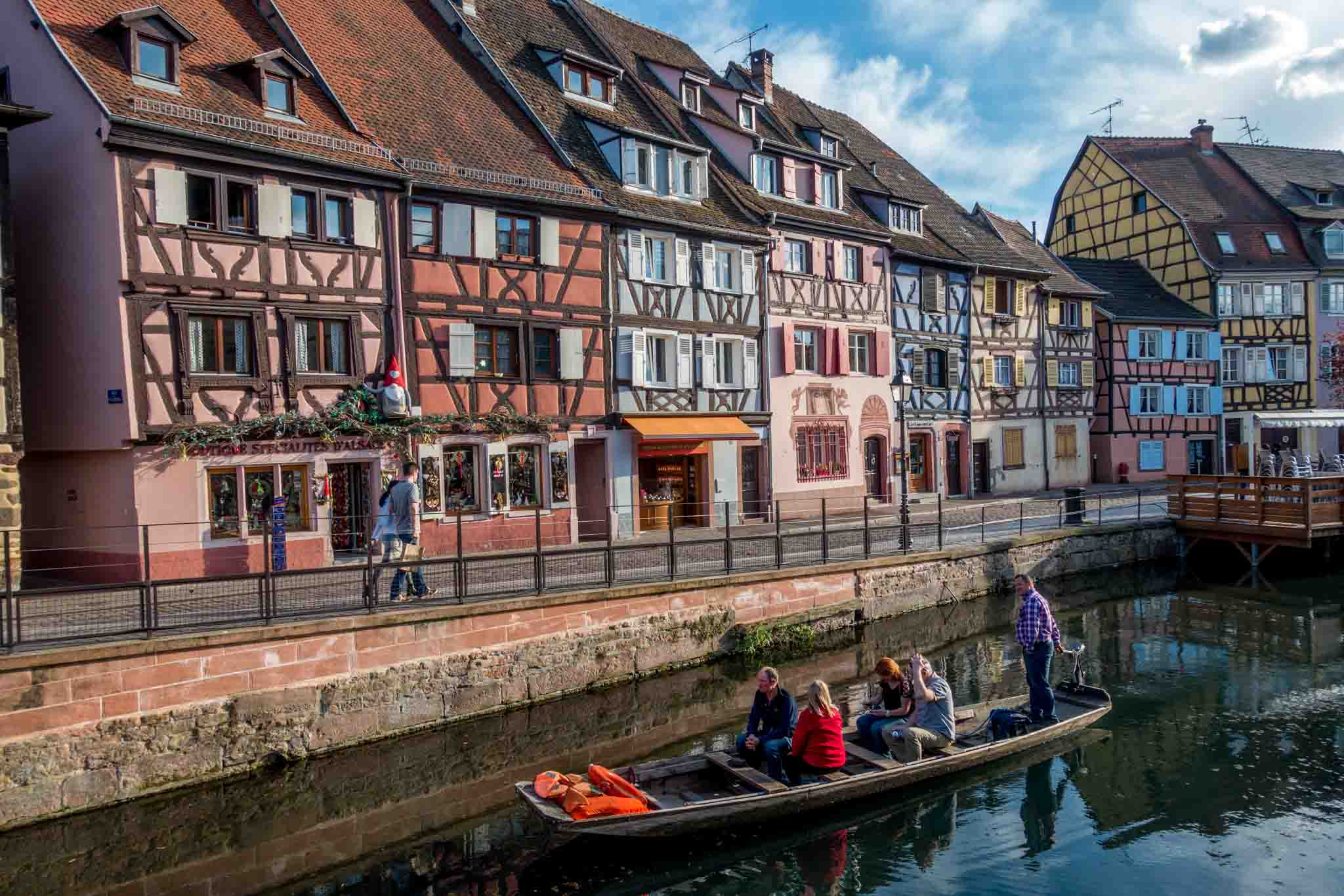 Boat in the river in front of a row of half-timbered buildings in Colmar