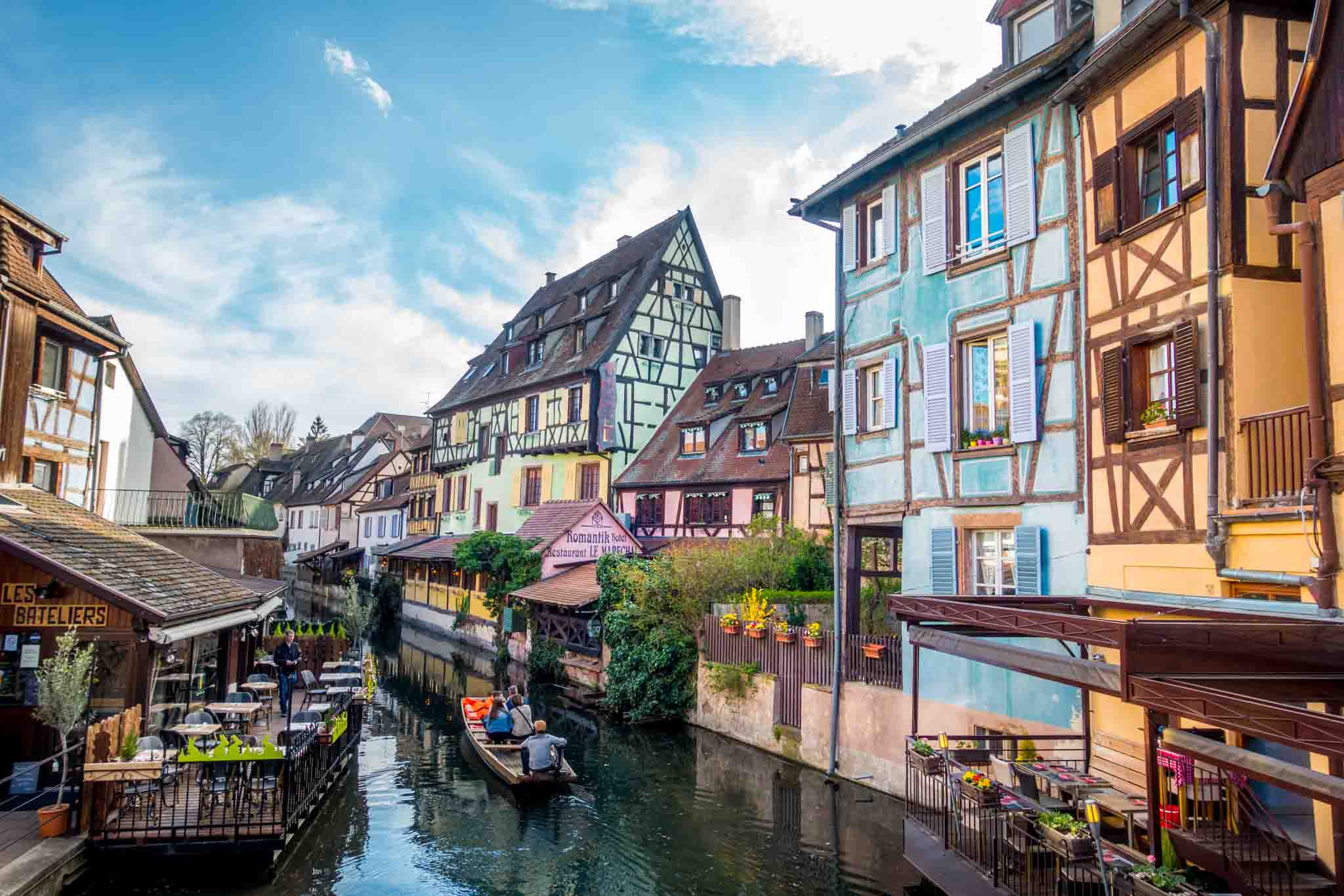 People in boat in a river passing by colorful buildings in Petite Venise in Colmar