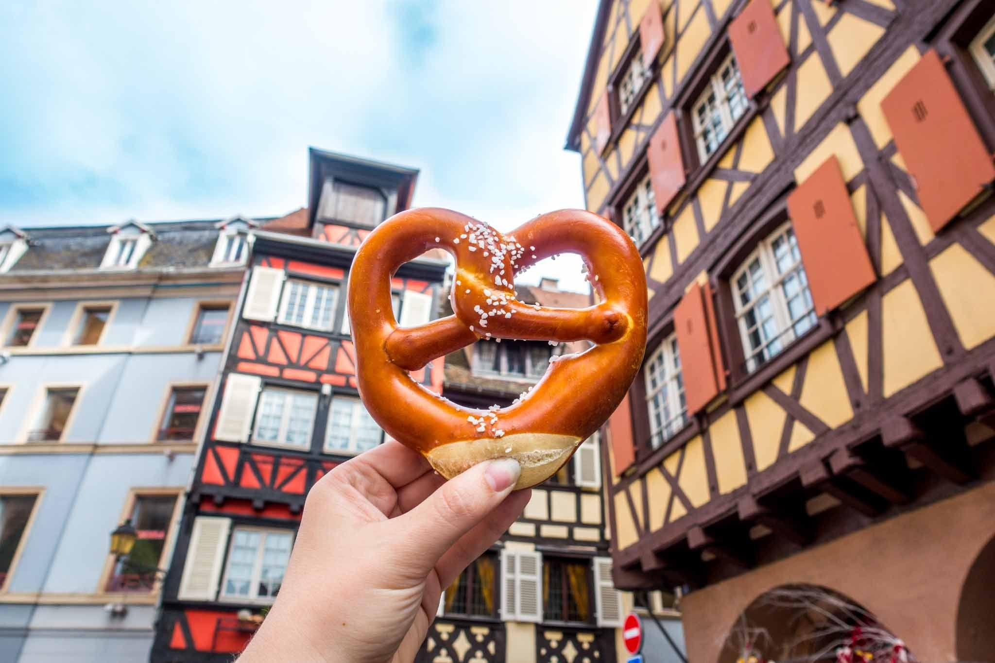 Pretzel in front of traditional Alsace buildings