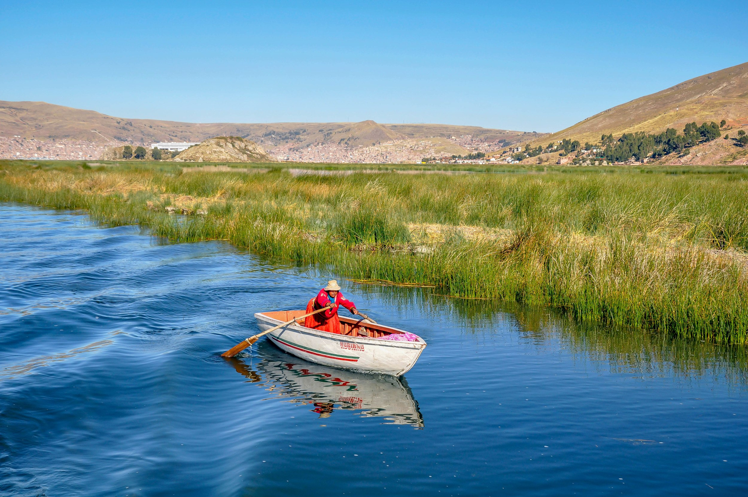 Woman in red dress rowing boat in Lake Titicaca, Peru