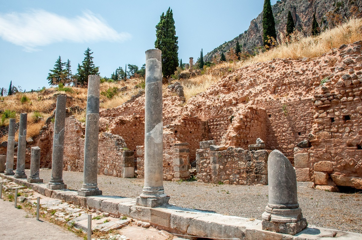 Columns and wall in the archaeological site of Delphi, Greece.  The site is sometimes called Delfi, Delfoi, or δελφοι.