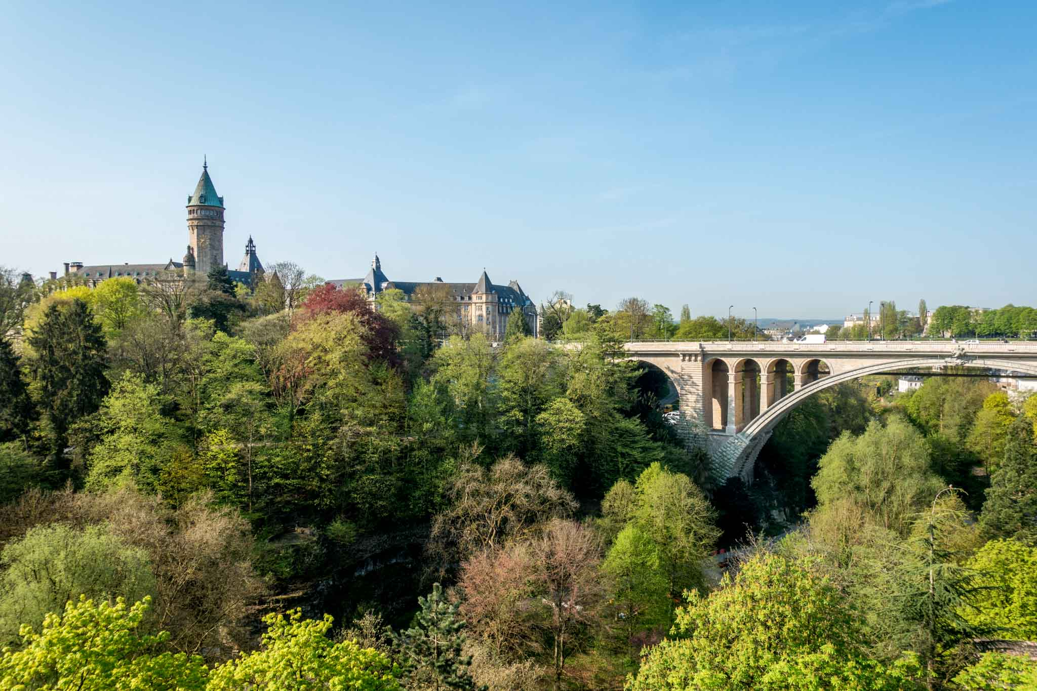 View of bridge and building across a tree-filled valley in Luxembourg City, Luxembourg