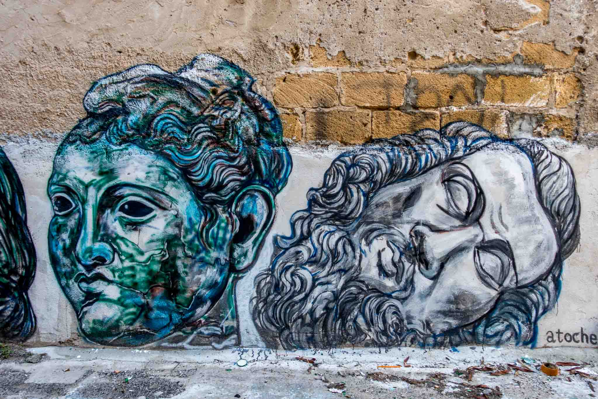 Two heads in a street art mural signed by artist Atoche