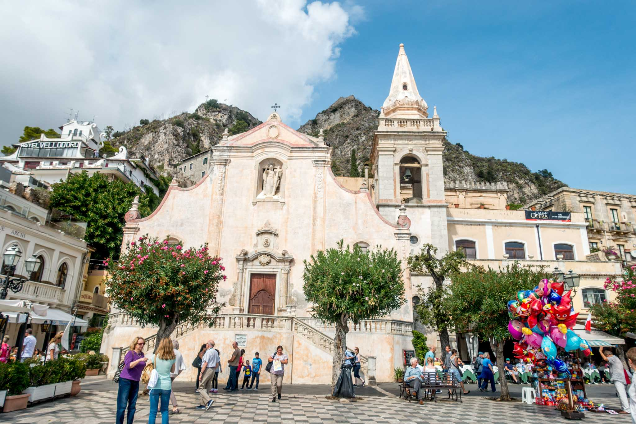 People in square in front of church in Taormina