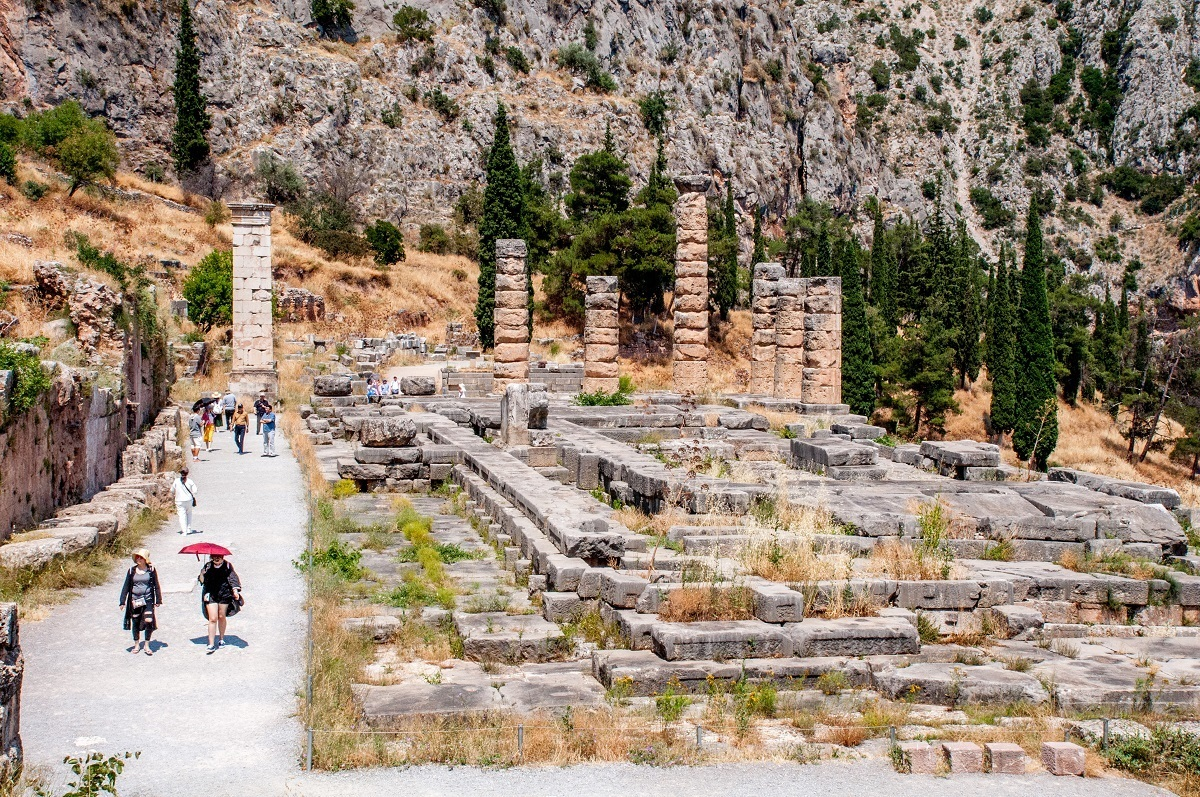 The Delphi Temple of Apollo.  Note the people with umbrellas and the lack  of shade.  It is hot at the ancient Delphi ruins.